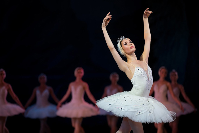 Prima ballerina white swan on stage dancing gracefully against other dancers. Ballet Swan Lake, the Opera House in Kiev, Ukraine.